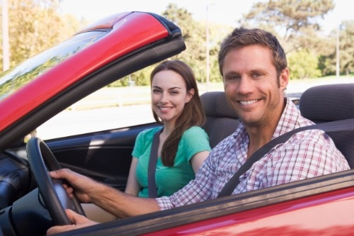 Couple with car insurance provide by their travel insurance by American Express Travel Insurance.
